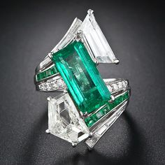 Spectacular Estate Emerald and Diamond Ring. large scale, adaptation of the classic platinum by-pass ring is designed around a vivacious, bright green, elongated emerald-cut emerald weighing 4.00 carats. The emerald is asymmetrically framed by two large fancy-cut diamonds: an epaulet-cut diamond weighing 2.25 carats and a trapezoid-cut diamond weighing 1.75 carats. The shoulders of the shank is enhanced by round brilliant and baguette-cut diamonds and rectangular-shaped calibre emeralds.