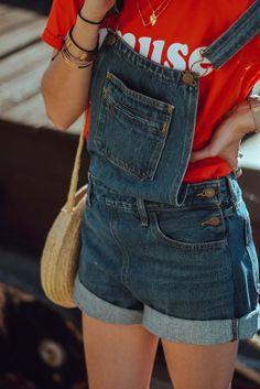 La salopette short en jean est de sortie ! Associée à un t-shirt orange, un panier en osier et des petites lunettes rondes pour un look rétro à souhait !