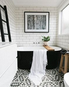 Modern bathroom with subway tiled walls, graphic caustic cement tiled floors and a bold black freestanding bathtub.