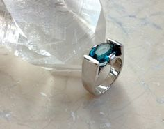 Faceted natural and untreated Blue Tourmaline ring hand crafted in rhodium-plated 925-sterling silver -   You will have a striking gemstone fashioned by a master gem cutter in this piece.    This elegant ring is handcrafted in 925 sterling silver and RHODIUM PLATED . Rhodium plating is used to increase the strength, durability, and bright look of silver.     Rhodium (like gold) is a low tarnish metal and therefore remains bright and shiny under most environmental conditions. It enhances the…