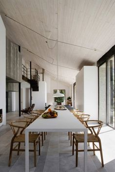 Simple very long dining table with lots of lovely Wishbone chairs by the Danish designer Hans Wegner...