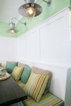 This kitchen features a beautiful dining area in this built-in banquette. The cool green of the wall is offset by the crisp white panelling and multi-colored upholstery in the booth and pillows. Built In Seating, Interior Design, Decorating Basics, Home, Interior, White Paneling, Home Decor, Floor Design, Room