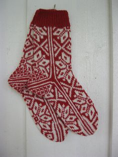 Handknitted norwegian socks for women in red with white pattern.