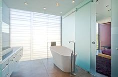 Modern Metal Towel Rack In A Minimalist Bathroom With Stylish White Bath Tub Design Near Window And The Floating Vanity