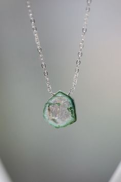 A one of a kind slice of watermelon tourmaline hangs suspended from a sterling silver link chain, which has been lightly hammered for shine. The
