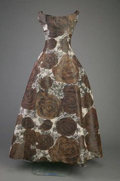 "Evening Dress, Christian Dior, Paris, France: 1953, silk taffeta print, tulle. ""The bell-shaped skirt and overall silhouette of this dress requires a complex understructure to support the shape. The dress's understructure is made up of nine layers of gathered net, all stitched to a torso-length girdle. This understructure provides the shape of the skirt, cinching the waist and torso while providing support for the breasts. The wearer simply ""stepped in"" to the gown to be ready for the…"