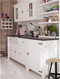 Mit diesen Möbeln können Sie Ihre eigene Landhausküche gestalten. Ob Spüle mit viel Stauraum, einen Oberschrank mit Türen, ein offenes Wandregal sowie Unterschränke mit links oder rechts angeschlagener Tür an. Die Türbeschläge ähneln alten Kühlschrankgriffen. Alle Möbel sind aus massiver Kiefer und sind weiß gestrichen. Die Arbeitsfläche ist schieferfarben mit einer wasserfesten Farbe gestrichen. Das Spülbecken ist aus Porzellan.