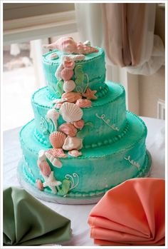 A turqoise wedding cake, decorated with a flow of artificial seashells and starfishes from top to bottom.