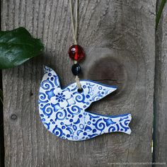 This beautiful one-of-a-kind bird was formed using the hand-built method with high-fire porcelain, then textured and fired to bisque and then glazed with lead-free blue color glaze glaze and high fired again in my kiln at my studio.  I finished adding a red and blue glass bead on a natural hemp cord. Ceramic birds by KerenOrHandmade on Etsy