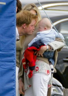 Prince Harry with Autumn Phillips who holds holds Savannah Phillips, grandchild of Princess Anne.