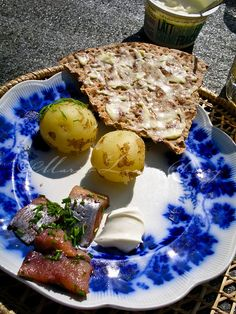 Typical Swedish summer  lunch plate of pickled matjes herring (sill) with chives, sour cream and boiled potatoes. Served with buttered crispbread and a glass of pilsner beer, outdoors.