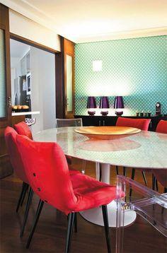 Na sala de jantar, a mesa Tulipa, de Eero Saarinen, acompanha cadeiras com camurça vermelha e pés palito, trazendo o estilo dos anos 1950. O contraponto contemporâneo aparece nas peças de acrílico (Inove Design).