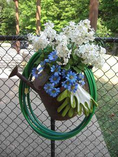 décoration jardin en arroisoir, fleurs, gants et tuyau d'arrosage