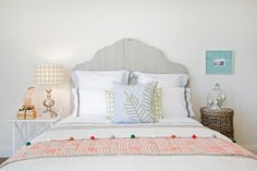 Pale+blues+and+hints+of+coral+create+a+soothing+color+palette+in+this+coastal-style+bedroom.+The+gray+wood-plank+headboard+brings+a+soft+yet+rustic+look+to+the+bed.+A+cloche+with+fake+flowers+makes+a+simple+but+pretty+floral+display+on+the+wicker+nightstand.