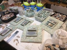 Sue is working on mixed media assemblages.  Clay, beach stones, leaves, fossils, twigs, acrylic paint.