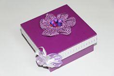 Caixinha em MDF na cor roxo com flor de tecido na parte superior, fita e laço de cetim na lateral da tapa. R$ 20,00
