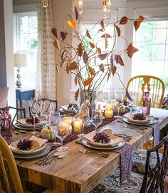 Photographer Lia Griffith used a woodland motif—note the natural wood, plum colored place cards, and twig-style silverware—to transform her dining room table into a beautiful natural scene.  See more at Lia Griffith.   - CountryLiving.com