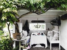 Backyard shed converted to a pretty, shabby chic entertaining nook. Delightful!