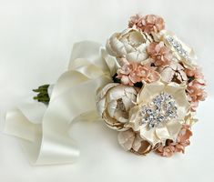 This silk fabric bridal bouquet is comprised of hand cut and formed flowers of various gorgeous silk fabrics in blush, champagne and ivory. Each flower has its own hand placed highlights featuring either rhinestones, crystals or genuine freshwater pearls. Completely handmade and stunning!Each flower is its own individual piece with a green dupioni silk wrapped stem that can be molded to any direction. This arrangement can be taken apart and arranged differently if desired.Me...