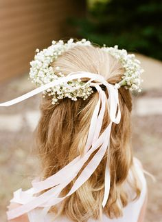 The flower girl will wear a halo of white baby's breath with ivory ribbon accents.
