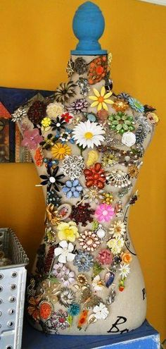 instead of stashing your colorful brooches away in drawer, display them on a dress form for everyone to see.