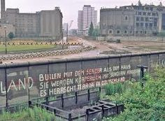 Looking over into Communist East Berlin from viewing platform...look over the wall at your own risk.  Broken glass inbedded in cement top of wall along with barbed wire.  German shepherd dogs patrolled beyond the tank traps. Armed patrolling soldiers & soldiers in towers.