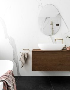 A monochrome bathroom with a timber vanity and gold tapware.
