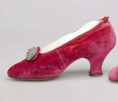 1910 Pumps of dark pink silk velvet. Pointed toe; circular rhinestone buckle attached to vamp and backed by slightly larger circle of self-fabric; self-fabric baby French heel. By J. Thomas, Paris.