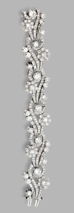 PLATINUM AND DIAMOND BRACELET. Of floral design set with baguette, old European-cut and single-cut diamonds weighing a total of approximately 23.60 carats, length 6¾ inches, one diamond missing.
