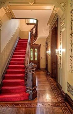 Foyer of 18th century Victorian mansion, with a hand-carved newell, wood staircase, and hardwood floor with decorative Greek key border inlays.