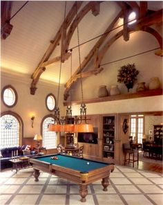The billiard light has to drop an impressive number of feet to meet the table. Great looking billiard room.