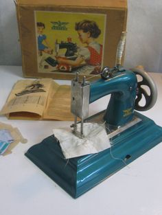 40s: Casige children sewing machine. Metal, petrol blue metallic. In original box with instructions. Made in Germany British Zone. Vintage