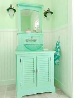 A large dose of Seafoam Green looks very colorful in this small cottage style bathroom with a very modern style glass sink!