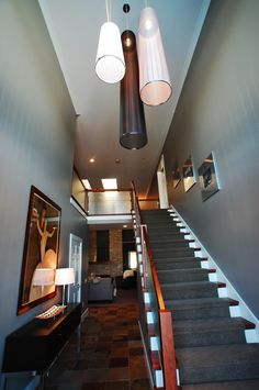 Entryway with Italian custom lighting. Cherry stair railing with glass panel inserts. Slate flooring, gray paint on walls. #entry #stairs