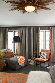 Deep gray walls and window treatments create a dramatic, moody space, but it's the orange drape liners that add unexpected brightness and tie the room together.