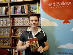 """Author and """"Glee"""" star Chris Colfer poses with his newest book, """"The Land of Stories: A Grimm Warning,"""" at the Red Balloon Bookshop on Grand Avenue in St. Paul on Wednesday, July 16, 2014."""