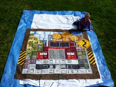 Logging Truck quilt made for her brother by Mary Zawlocki.   (This big quilt ends at the dark borders. It has been put on a blue tarp that has a light fabric over it. The quilter is in the photo but she does not show up well.)