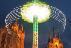 In a five second time exposure a carousel rotates in front of the Mariendom (Cathedral of Mary), left, and the St. Severi's Church, right, during the Oktoberfest in Erfurt