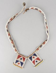 Narrow beaded necklace (?) of plaited vegetable fibre, fastened by means of a single small brass button at one end, and strung with glass beads in alternate red and dark blue rectangular motifs on a white background, and with two rectangular central panels of geometrical patterns also in red and dark blue on a white background. The panels have a row of larger yellow beads along their lower edge l Made by Zulu (?) l 19thC-20thC.
