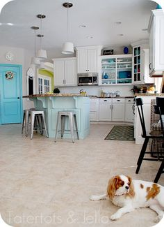 aqua and white kitchen. pop of green in dining room, black kitchen table, painted over kitchen tiles.