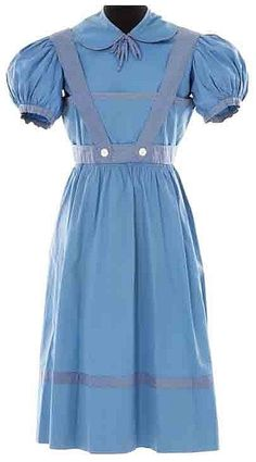 """Judy Garland early """"Dorothy"""" dress from The Wizard of Oz. (MGM, 1939)  Designed by legendary MGM costume designer Gilbert Adrian, the dress is a blue cotton dress with polka dot trim with blue cotton puff-sleeve blouse with matching trim. Judy Garland wore this style dress for the first two weeks of filming in October 1938 under director Richard Thorpe when Buddy Ebsen was the """"Tin Man""""."""