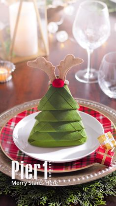Make your Christmas dinner guests feel extra special with a Noel napkin on each plate. It's easy! Step 1) Fold. Step 2) More folding. Step 3) Paper clip. Step 4) Napkin ring. Step 5) Make merry!