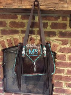 The Bonnie Bag, with the owners brand in turquoise suede on the flap and hand cut suede fringe on the straps. Custom purses and totes from gowestdesigns.us