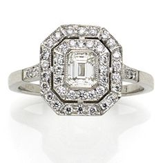 Octagonal target ring set with an emerald cut diamond ( .41 cts) framed by two lines of diamonds, each shoulder set with four diamonds, all diamonds pavé set in a platinum mille grain mount, the remaining diamonds totalling .27 carats. Catalogue No. 081H00328