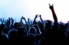 happy rock band: silhouettes of concert crowd in front of bright stage lights Stock Photo