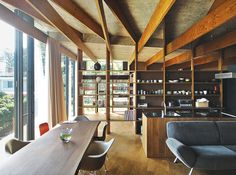Modern Japanese hilltop home living and dining area with custom kitchen island and stove vent along with Eames chairs