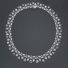 A DIAMOND NECKLACE   Composed of a series of circular-cut diamond scrolling links, each suspending a circular-cut diamond cluster, spaced by circular-cut diamonds, enhaced by pear-shaped rose-cut diamond terminals, mounted in platinum, 15 ins.  The total weight of the diamonds is approximately 23.00 carats