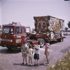 "Four children stand looking at a circus wagon labeled ""Pawnee Bill"" which is chained to the bed of an International truck. The wagon was part of a 25-piece circus parade that traveled from Circus World Museum in Baraboo to Milwaukee."