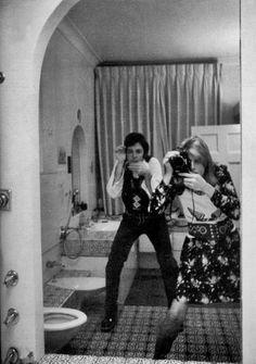 Linda McCartney taking a mirror self-portrait in a fancy-looking bathroom with Paul McCartney imitating her - Lomography