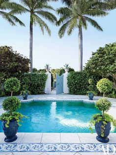 A plunge pool centers the front courtyard; the ceramic tiles and travertine pavers are by Country Floors.